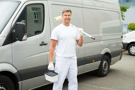 Photo pour Happy Mature Painter Standing In Front Of Van - image libre de droit