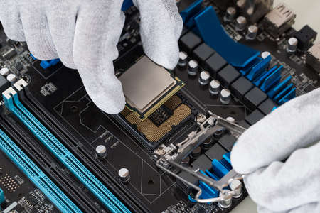 Photo pour Close-up Of Person Hands Installing Central Processor In Motherboard - image libre de droit