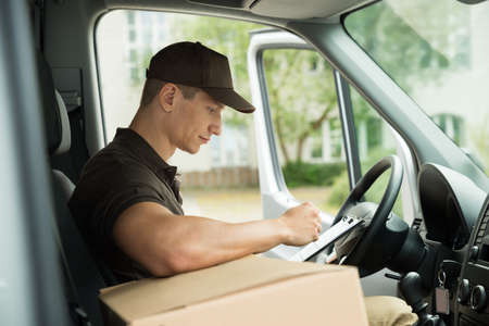 Photo pour Young Delivery Man Checking List On Clipboard In Van - image libre de droit