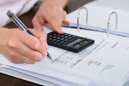 Photo pour Close-up Of Accountant Doing Calculation With Calculator In Office - image libre de droit
