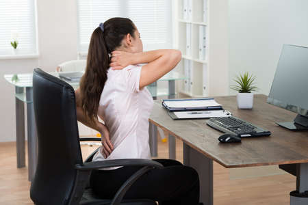 Photo for Young Businesswoman Sitting On Chair Having Backpain In Office - Royalty Free Image