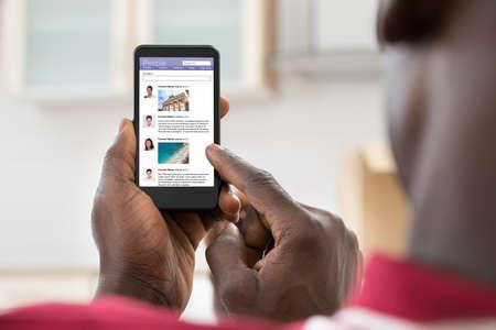 Foto de Close-up Of African Young Man Surfing On Social Networking Site Using Cellphone - Imagen libre de derechos