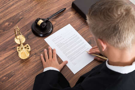 Photo pour Close-up Of Judge Writing On Paper In Courtroom - image libre de droit