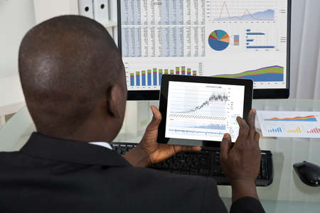 Photo pour Rear View Of Young African Businessman Analyzing Graph On Digital Tablet In Office - image libre de droit