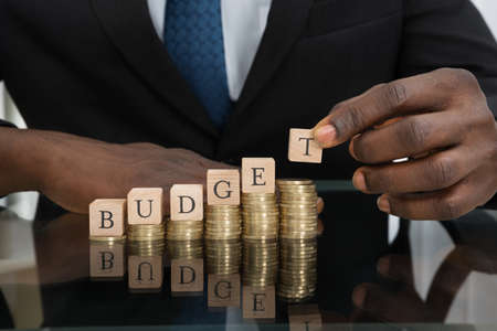 Photo pour Close-up Of Businessman Hands Putting The Letters Of The Word Budget On Stack Of Coins - image libre de droit