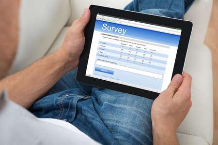 Photo pour Close-up Of Person On Sofa With Digital Tablet Showing Survey Form - image libre de droit