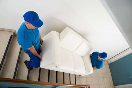 Foto de High Angle View Of Two Male Movers Carrying Sofa On Staircase Of House - Imagen libre de derechos