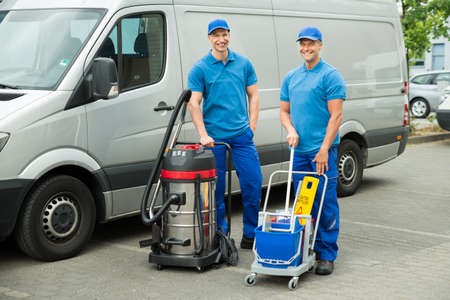 Photo pour Two Happy Male Cleaners Standing With Cleaning Equipments In Front Van - image libre de droit