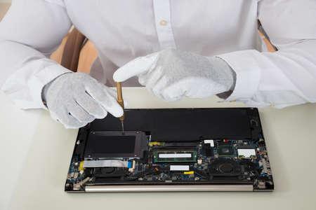 Foto de Close-up Of Technician Repairing Laptop At Desk - Imagen libre de derechos