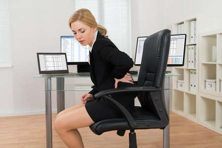 Foto de Young Businesswoman Sitting On Chair Suffering From Backache In Office - Imagen libre de derechos