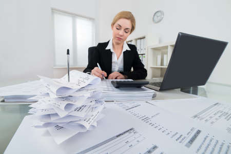 Photo pour Young Businesswoman Calculating Invoices And Taxes At Workplace - image libre de droit