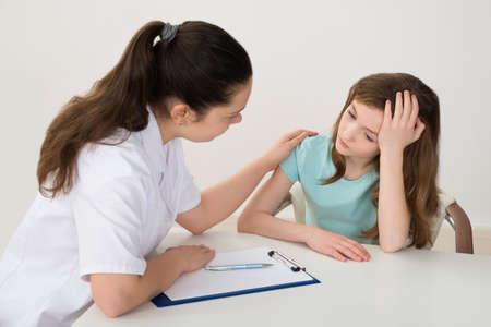 Foto de Female Doctor Comforting Depressed Patient Sitting At Table - Imagen libre de derechos