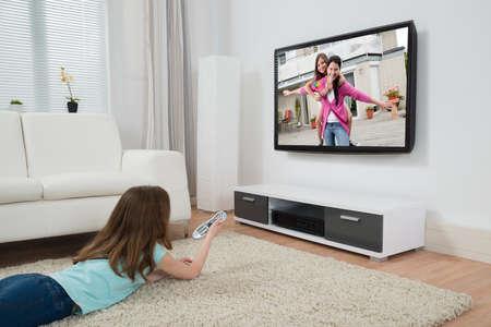 Foto de Girl With Remote Control Watching Movie On Television In Living Room - Imagen libre de derechos