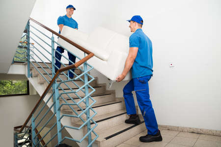 Photo for Two Happy Male Movers In Uniform Carrying White Sofa On Staircase - Royalty Free Image