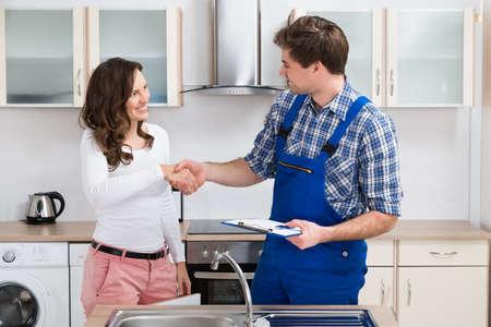 Foto de Young Woman Shaking Hands To Male Plumber With Clipboard In Kitchen Room - Imagen libre de derechos