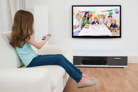Photo pour Girl Changing Channel With Remote Control In Front Of Television At Home - image libre de droit