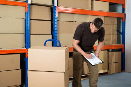 Foto de Male Worker With Cardboard Boxes Writing On Clipboard In Warehouse - Imagen libre de derechos