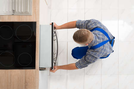 Photo pour High Angle View Of Man In Overall Repairing Oven In Kitchen - image libre de droit