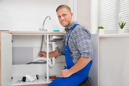 Foto de Happy Male Plumber Repairing Faucet In Kitchen Sink - Imagen libre de derechos