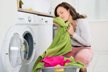 Foto de Young Woman Crouching With Cleaned Clothes Near The Electronic Washer - Imagen libre de derechos