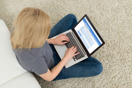Foto per Young Woman Sitting On Carpet With Laptop Filling Survey Form - Immagine Royalty Free