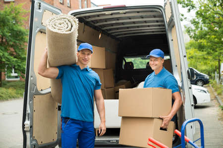Photo for Two Male Workers Carrying Carpet And Cardboard Boxes In Front Of Van - Royalty Free Image