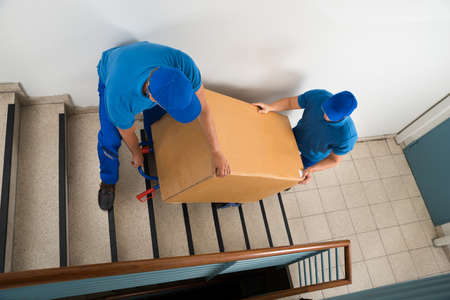 Photo for Two Male Movers Walking Downward With Box On Staircase - Royalty Free Image
