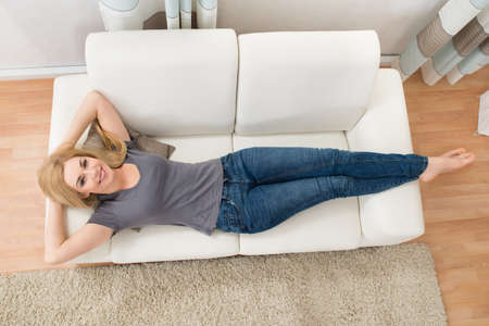 Photo for Young Happy Woman Lying On White Sofa At Home - Royalty Free Image