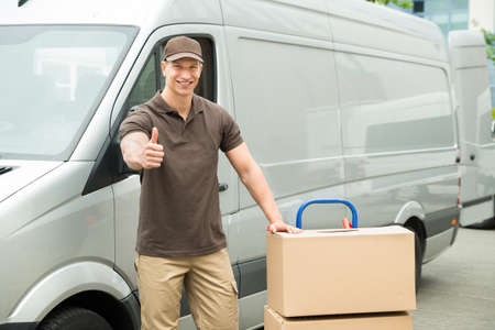 Photo pour Young Delivery Man In Front Van With Cardboard Boxes Showing Thumbs Up Sign - image libre de droit