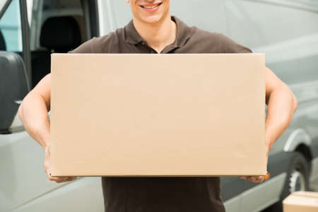 Photo pour Close-up Of Young Delivery Man Carrying Box In Hand - image libre de droit
