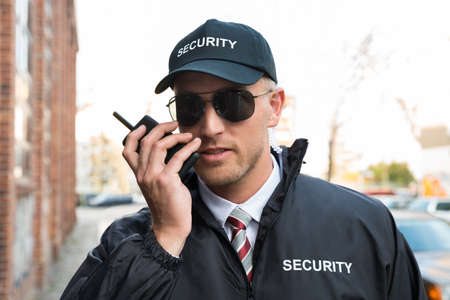 Foto für Portrait Of Young Male Security Guard Talking On Walkie-talkie - Lizenzfreies Bild