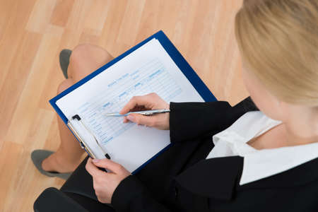 High Angle View Of Businesswoman Filling Blank Weekly Time Sheet In Office