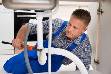 Foto de Male Plumber Repairing White Sink Pipe In Kitchen Room - Imagen libre de derechos