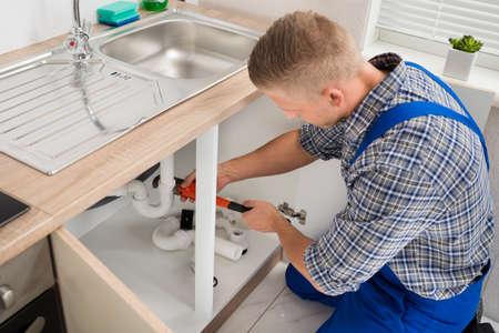 Foto de Male Plumber Fixing Sink Pipe With Adjustable Wrench In Kitchen - Imagen libre de derechos