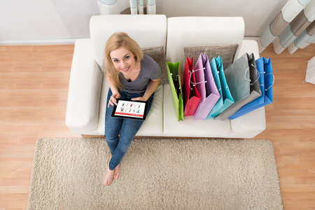Photo pour Young Woman Sitting On Sofa With Digital Tablet Shopping Online - image libre de droit