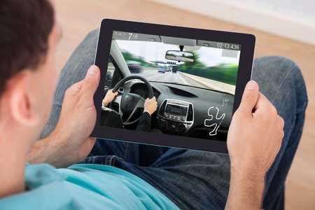 Photo for Young Man Playing Car Racing Game On Digital Tablet At Home - Royalty Free Image