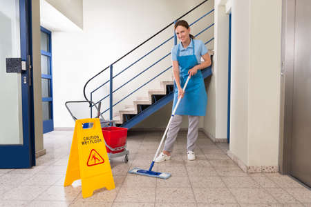 Photo pour Young Happy Female Worker With Cleaning Equipments And Wet Floor Sign On Floor - image libre de droit