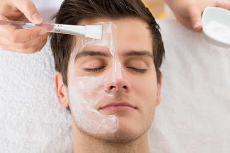 Photo pour Therapist Hands With Brush Applying Face Mask To A Young Man In A Spa - image libre de droit