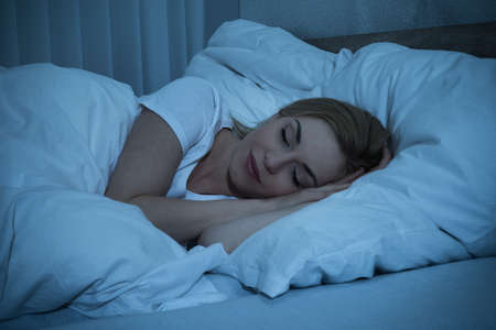 Photo pour Young Woman With Blanket Sleeping At Night In Bed - image libre de droit