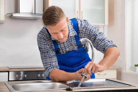 Foto de Young Repairman Installing Faucet Of Kitchen Sink In Kitchen Room - Imagen libre de derechos