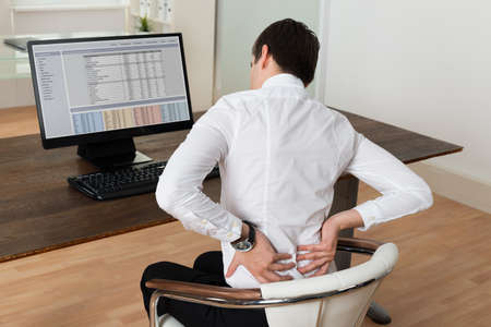 Photo pour Young Businessman Sitting On Chair And Suffering From Backache At Desk - image libre de droit