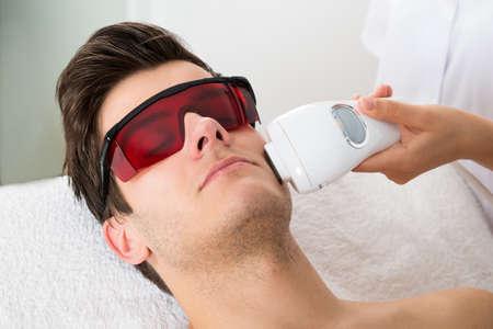 Photo pour Young Man Receiving Laser Hair Removal Treatment At Beauty Center - image libre de droit