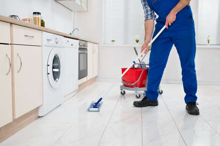 Photo pour Close-up Of Worker Cleaning Floor With Mop In Kitchen Room - image libre de droit
