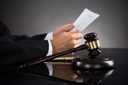 Foto de Close-up Of Judge Holding Document With Gavel At Desk - Imagen libre de derechos