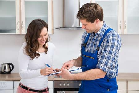 Foto de Happy Woman Writing On Clipboard With Male Plumber Standing In Kitchen Room - Imagen libre de derechos
