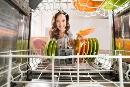 Photo pour Happy Woman Removing Plate View From Inside The Dishwasher - image libre de droit