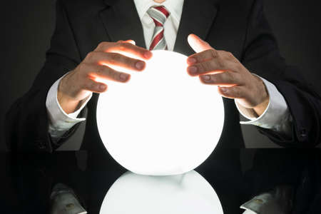 Photo pour Close-up Of Businessman Predicting Future With Crystal Ball At Desk - image libre de droit