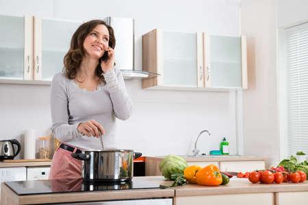 Foto de Happy Woman Talking On Mobile Phone While Cooking In Kitchen - Imagen libre de derechos