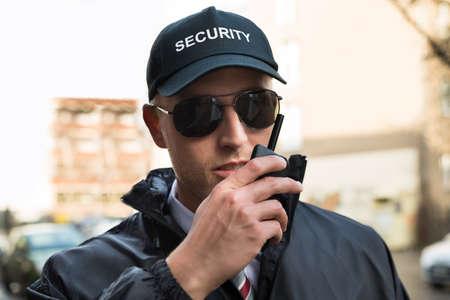 Foto de Portrait Of Young Male Security Guard Talking On Walkie-talkie - Imagen libre de derechos