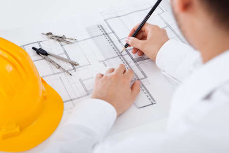 Photo pour Closeup cropped image of a young male architect working on blueprints spread out on a table - image libre de droit
